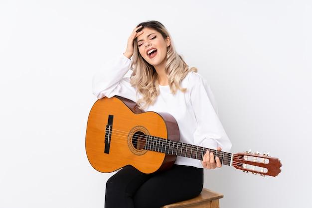 Het tienermeisje met gitaar over geïsoleerde witte achtergrond heeft iets gerealiseerd en de oplossing voornemens