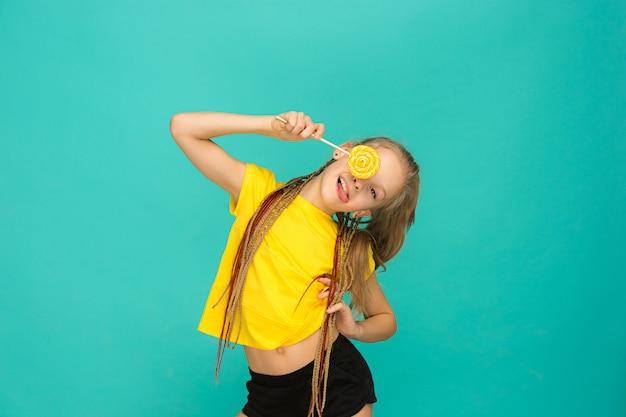 Het tienermeisje met kleurrijke lolly op een blauw
