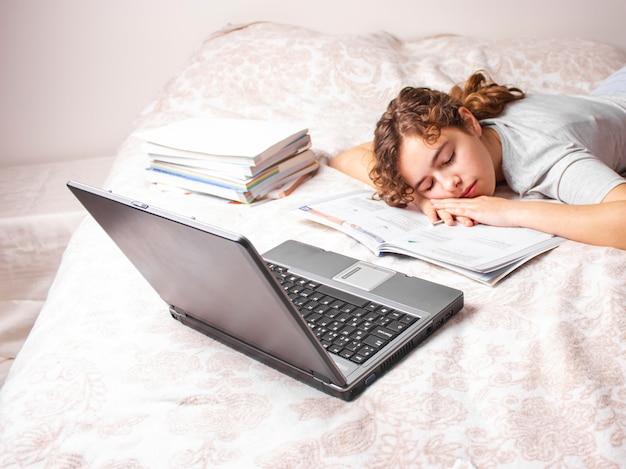 Het tienermeisje op quarantaine bestudeert online op haar bed. het meisje slaapt voor laptop
