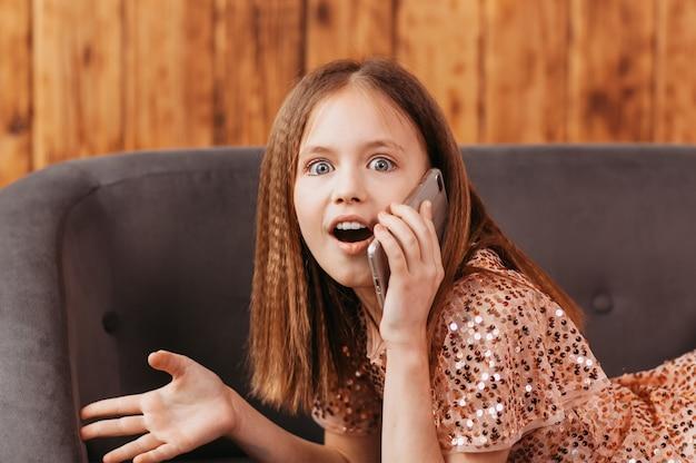 Het tienermeisje praat aan de telefoon en is verrast. emoties en expressie