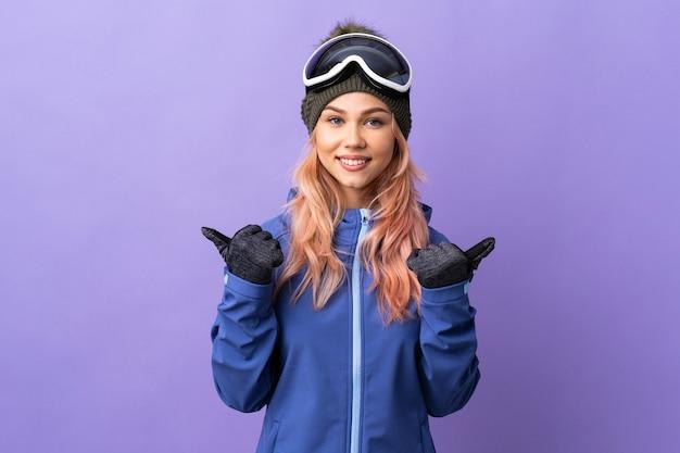 Het tienermeisje van de skiër met snowboardbril over geïsoleerde purpere muur met duimen op gebaar en het glimlachen