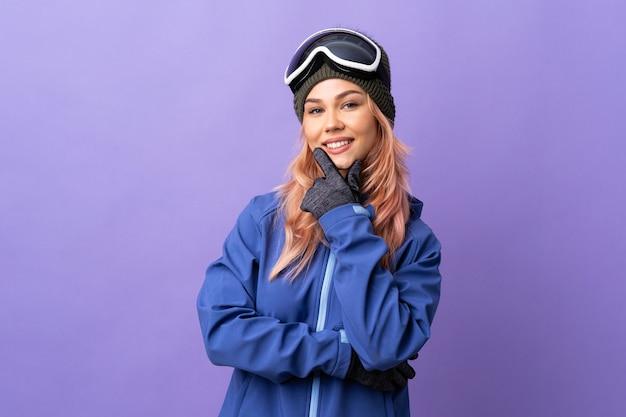 Het tienermeisje van de skiër met snowboardglazen over geïsoleerde purpere gelukkig en glimlachende muur