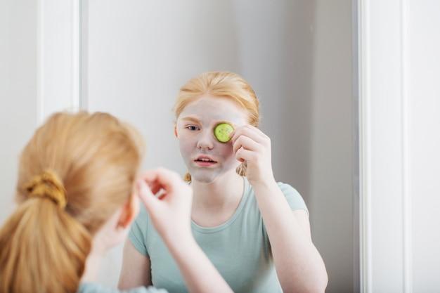 Het tienermeisje zet gezichtsmasker op