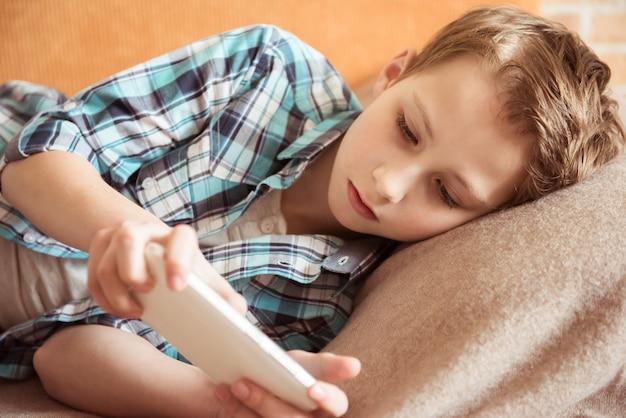 Het tieneroverseinen aan vrienden babbelen op mobiel thuis liggend op laag in woonkamer