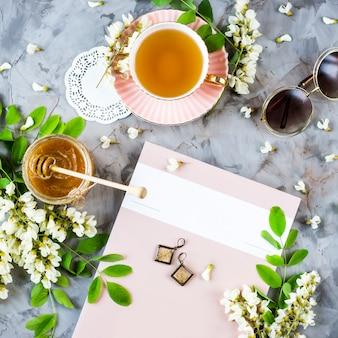 Het tijdschrift naast een kopje thee en een pot honing, tussen de bloeiende acacia