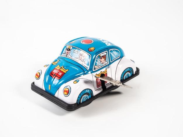 Het tinstuk speelgoed van de auto op wit