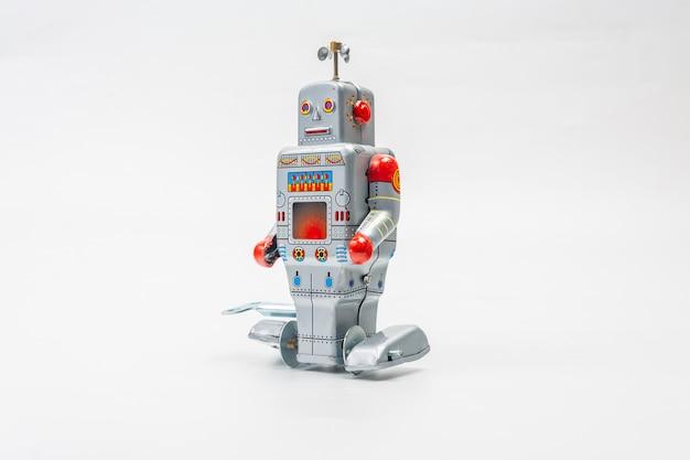 Het tinstuk speelgoed van de robot op witte achtergrond