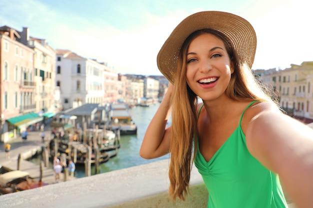 Het toeristenmeisje van venetië op de rialtobrug die selfie foto met het beroemde canal grande op de achtergrond neemt