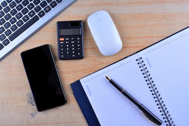 Het toetsenbord met muis, vulpen, notitieboekje, rekenmachine en smartphone op tafel
