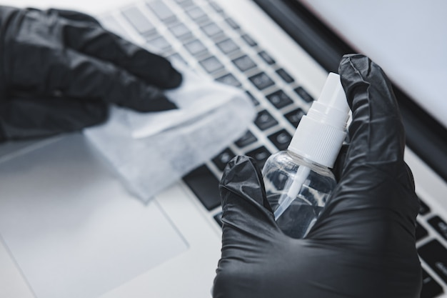 Het toetsenbord van de laptop schoonmaken met een ontsmettingsmiddel. concept van hygiëne en preventie van virusverspreiding op het werk of thuis