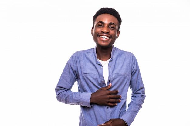 Het toevallige jonge afrikaanse mens stellen voor camera die op witte muur wordt geïsoleerd