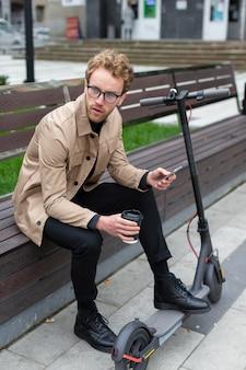 Het toevallige mannelijke stellen met een elektrische autoped