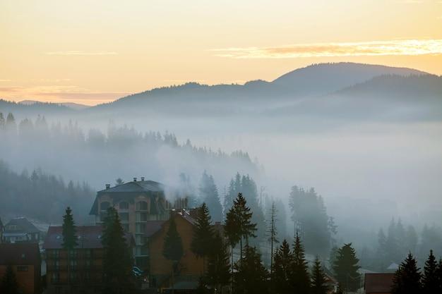 Het toevluchtdorp huisvest gebouwen op achtergrond van mistige blauwe bergheuvels die met dicht nevelig net bos onder heldere roze hemel bij zonsopgang worden behandeld. berglandschap bij dageraad.
