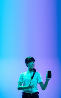 Het tonen van het lege telefoonscherm het portret van de jonge aziatische vrouw op gradiëntblauwpaarse studio