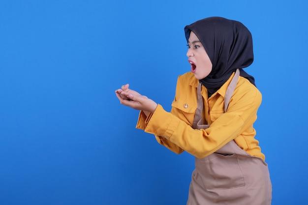 Het tonen van mooie vrouw die schort draagt die iets op haar handen toont