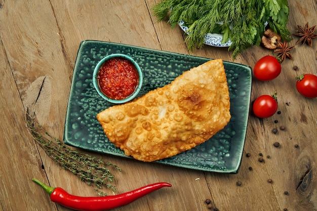Het traditionele blanke gerecht is cheburek, een gebakken taart in olie met verschillende vullingen, voornamelijk vlees of kaas op een blauw bord.