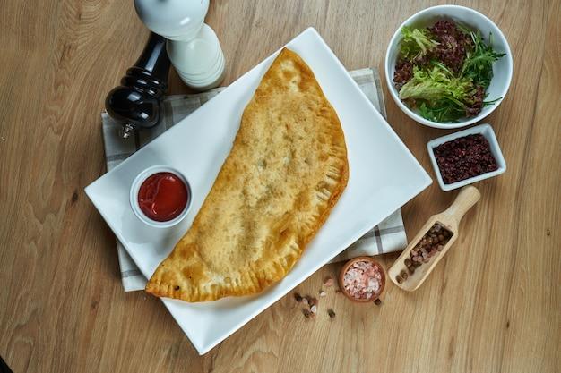 Het traditionele kaukasische gerecht is cheburek, een gebakken taart in boter met verschillende vullingen, voornamelijk vlees of kaas op een wit bord. plat eten