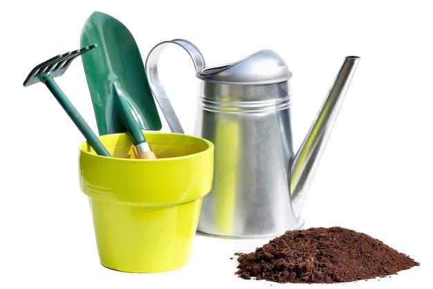 Het tuinieren hulpmiddelen in een pot en gieter op witte achtergrond