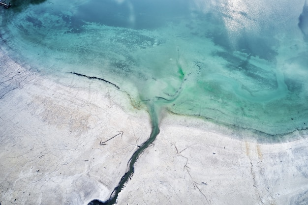 Het turquoise water van de zee naast de kust met gravures van pijlen