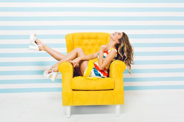 Het uiten van heldere positieve emoties van vrolijke modieuze jonge vrouw in kleurrijke jurk met plezier in gele stoel geïsoleerd op gestreepte blauw witte muur. zomertijd, vreugde, glimlachen, geluk.