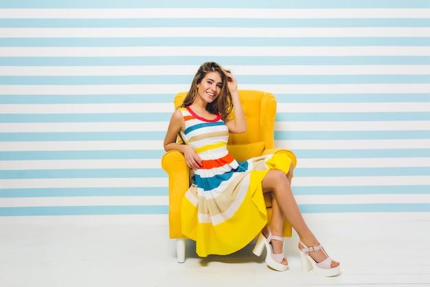 Het uiten van heldere positieve emoties van vrolijke modieuze jonge vrouw in kleurrijke jurk met plezier in gele stoel op gestreepte blauw witte muur. zomertijd, vreugde, glimlachen, geluk.