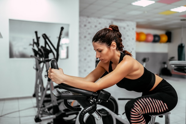 Het uitoefenen van benen die cardiotraining op fiets doen fiets.