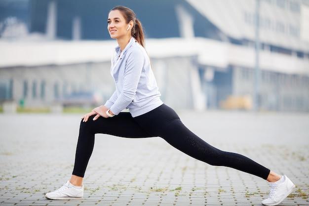 Het uitrekkende lichaam van de vrouw, die oefeningen op straat doet