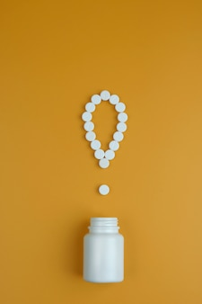 Het uitroepteken van de pillen uitroeppunt. witte pillen op een gele achtergrond. belangrijke informatie over medische onderwerpen.
