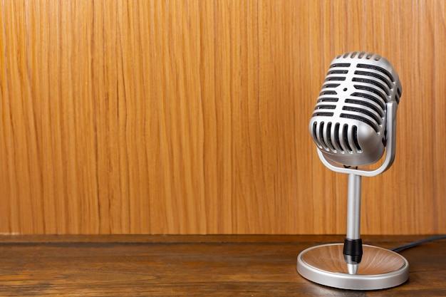 Het uitstekende microfoon dichte omhooggaande beeld op houten achtergrond.