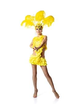 Het uitvoeren van. mooie jonge vrouw in carnaval-maskeradekostuum met gele veren die op witte achtergrond dansen. concept van vakantieviering, feestelijke tijd, dans, feest, geluk. copyspace