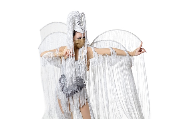 Het uitvoeren van. mooie jonge vrouw in carnaval-maskeradekostuum met witte veren die op witte achtergrond dansen. concept van vakantieviering, feestelijke tijd, dans, feest, geluk. copyspace
