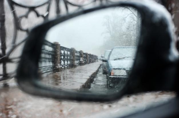 Het uitzicht in de zijachteruitkijkspiegel van de auto bij slecht weer