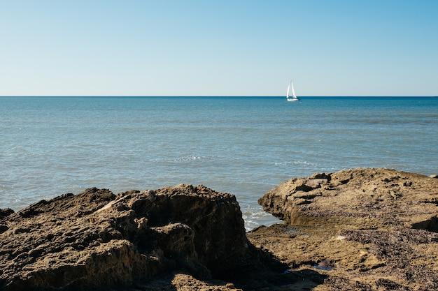 Het uitzicht op de middellandse zee, kleine jacht en rotsen