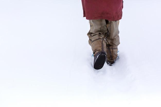 Het uitzicht vanaf de achterkant van een man die in de sneeuw loopt in rubberen laarzen
