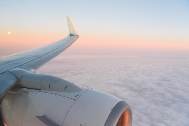 Het uitzicht vanaf de belichting van het vliegtuig naar de vleugel, vliegtuigturbine en pluizige wolken bij zonsopgang. vliegen over de wolken