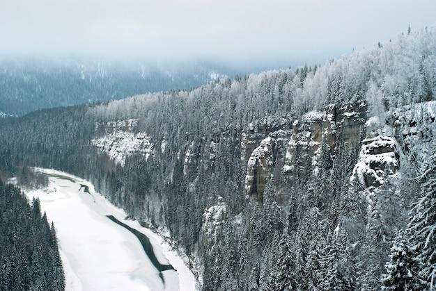 Het uitzicht vanaf de top van de rots naar de bevroren rivier in het winterlandschap