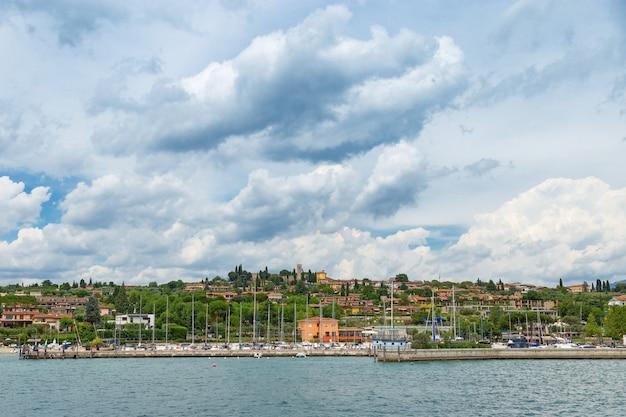 Het uitzicht vanaf het water op de kust van het kleine italiaanse stadje manerba del garda. natuurlijke omgeving van het gardameer.