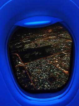 Het uitzicht vanuit het vliegtuig naar de lichten van de nachtstad.