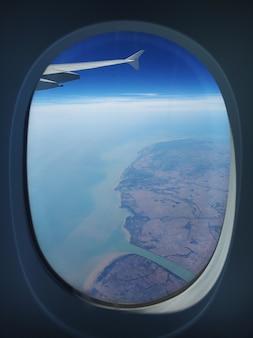 Het uitzicht vanuit het vliegtuigraam naar de grond. landschapsmening vanuit de lucht.