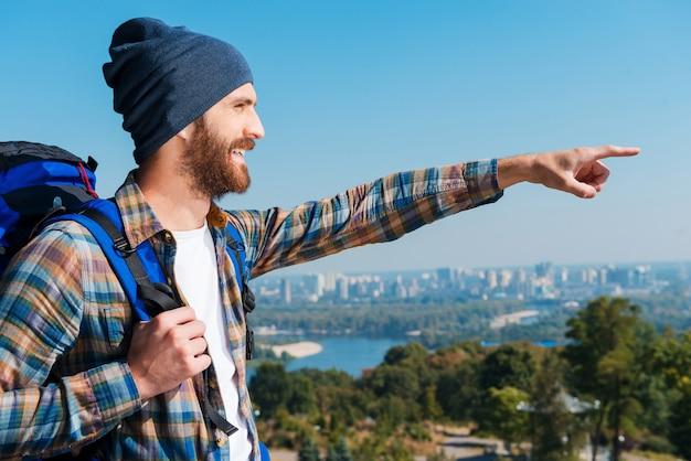 Het uitzicht waarderen. zijaanzicht van een knappe jongeman met een rugzak die wijst en wegkijkt met een glimlach