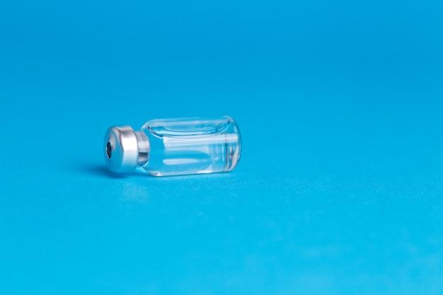 Het vaccinfles van de close-up op blauw geïsoleerde achtergrond. geen inscriptie, leeg voor reclame.