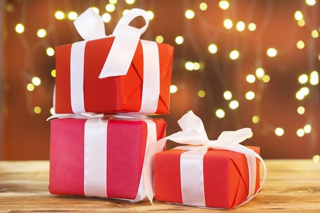 Het vakje van de kerstmisgift op houten lijst tegen bruine bokehachtergrond
