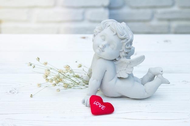 Het valentijnskaart rood hart van het liefdebericht met cupid steen op witte baksteenachtergrond