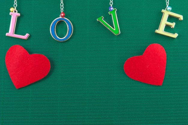Het van letters voorzien van de liefde met 2 harten hangt op groene achtergrond, valentijnskaartconcept
