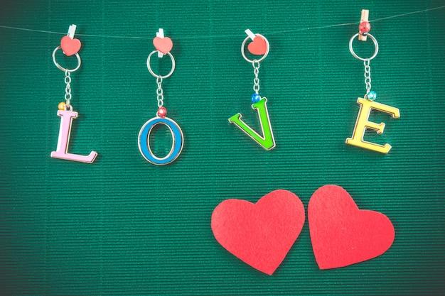 Het van letters voorzien van de liefde met 2 rode harten hangt op groene achtergrond, valentijnskaartconcept