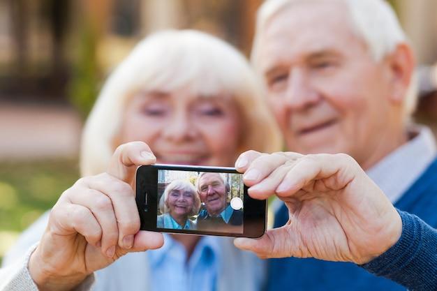 Het vastleggen van de eindeloze liefde. gelukkig senior koppel hecht zich aan elkaar en maakt selfie terwijl ze buiten staan