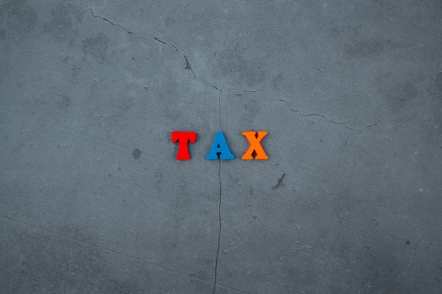 Het veelkleurige belastingwoord is gemaakt van houten letters op een grijze gepleisterde grond.