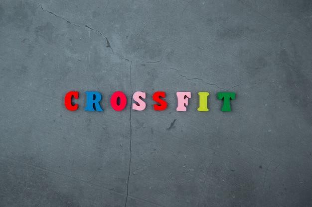 Het veelkleurige crossfit-woord is gemaakt van houten letters op een grijs gepleisterde muur.