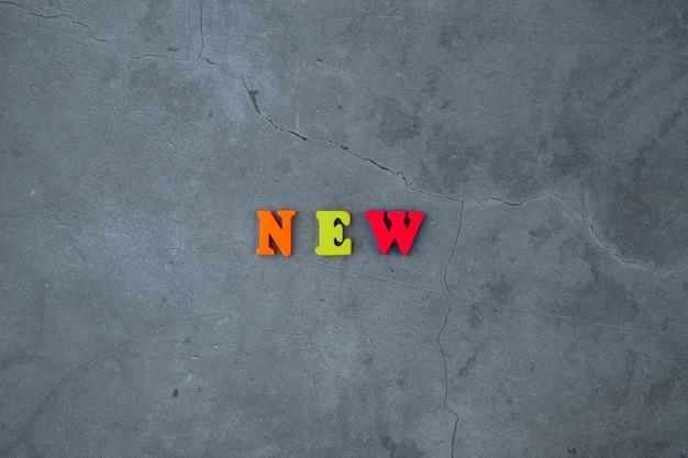 Het veelkleurige nieuwe woord is gemaakt van houten letters op een grijze gepleisterde muur.