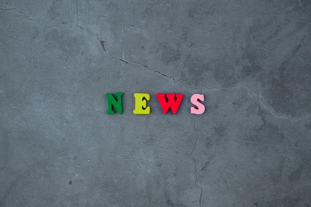 Het veelkleurige 'nieuws'-woord is gemaakt van houten letters op een grijze gepleisterde muur.